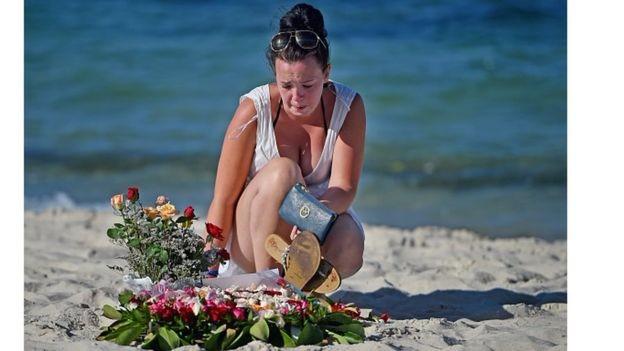 Жінка покладає квіти на місці загибелі туристів на пляжі Мархаба, Туніс